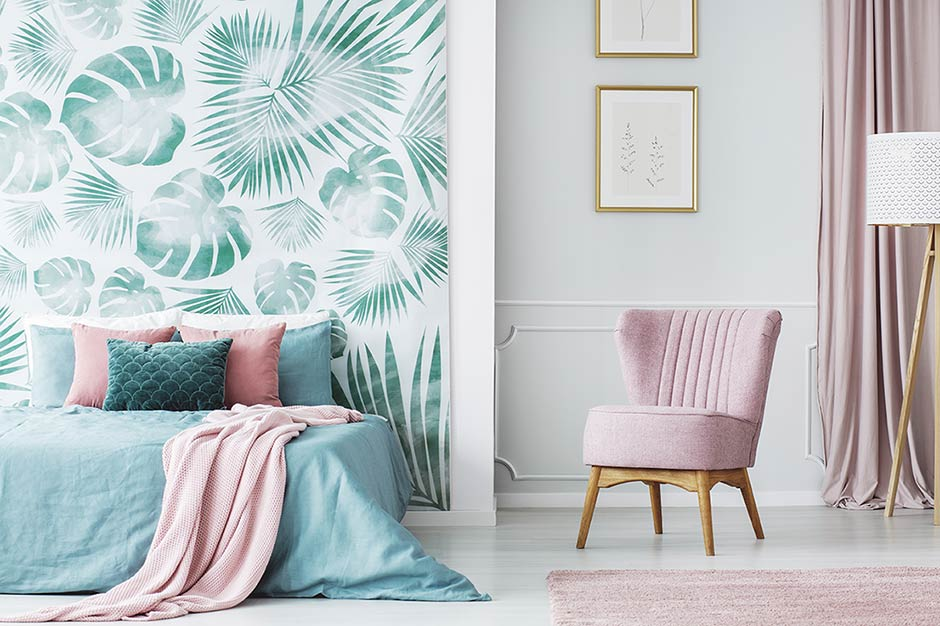 Bedroom with leafy accent wall and pink chair.